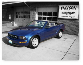 Repaired Mustang in front of Collision Shop